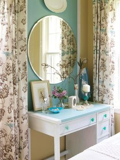 The bedroom windows are dressed with shower curtains, an affordable and unexpected alternative to pricey drapes. The oval mirror introduces another vintage item to the room. The old childhood desk was updated with paint and blue glass knobs