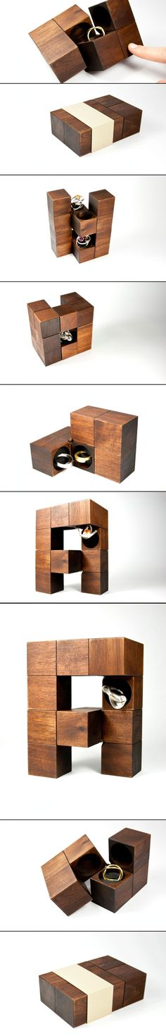 KLOTZ is handmade out of 6 wooden cubes. The walnut wood is treated and colored with natural oil. 3 cubes are then joined together and connected with a leather strap. The ring is fixed with the help of an inlay made from foam rubber. A paper loop is used as an individually shaped elegant closure, a logo can easily be printed onto it. This wooden box does not only protect it's precious content, it can also accentuate and highlight it.