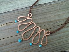 Handmade wire copper   necklace with turquoise stones and   brown cord .. $27.00, via Etsy.