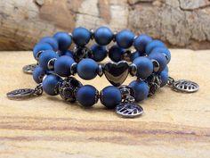 Conjunto com 2 pulseiras em fio de silicone (elástico). <br>Primeira pulseira com bolinhas em resina na cor azul royal, com bolinhas em metal grafite cravejadas de strass, e pingentes em formato de mandala com strass (cristal) azul royal. <br>Segunda pulseira com bolinhas em resina azul, entremeios em formato argolas e coração, em metal grafite. <br>Altura das 2 pulseiras juntas: 2 cm <br>Comprimento: 18,5 cm <br>Prazo para postagem: 02 dias úteis após confirmação do pagamento