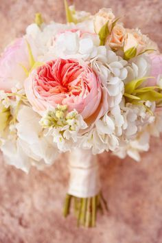 This bouquet consists of white hydrangeas, garden roses, spray roses, & white stock