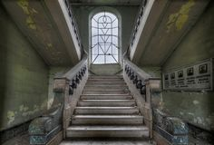 Steps for the lost - Massive concrete staircase inside a former orphanage. Unfortunately the stained glass in the window has probably been shattered a long time ago and just a small piece of purple glass at the top hints of how stunning it once looked.