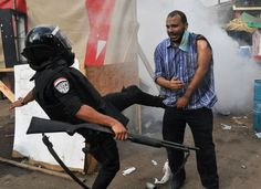 An Egyptian security force member kicks a wounded supporter of ousted President Morsi the clearing of a sit-in camp near Cairo University, on August 14, 2013. (AP Photo/Hussein Tallal)