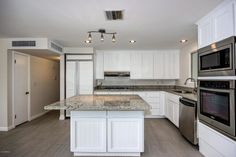 Sold   Sonoran Lauren Modern, gray kitchen. Granite, stainless steel, white cabinetry.