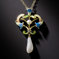 "Art Nouveau Enamel and Pearl Pendant. A sinuous trio of shimmering blue and green enamel morning glories form the centerpiece of this enchanting Art Nouveau necklace centered with a lustrous freshwater pearl, a tiny twinkling diamond with a freshwater 'wing' pearl dancing below. An ultra-lovely nature-inspired jewel - circa 1900. 1 1/4 by 13/16 inch; 16"" chain."