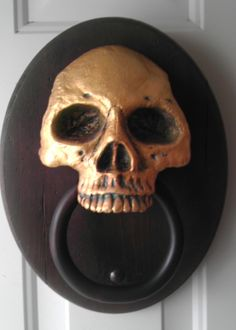 "A ""haunted"" door knocker made from Durham's Water Putty. The skull portion is solid Water Putty and painted to look like bronze. The knocker has a sensor and motor drive hidden in it. As people approach, the knocker starts knocking on its own. Despite years of use and hundreds of hours of knocking, you can see the Water Putty has held up perfectly."