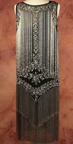 The beading on this dress says it all. Rich, dense layers of flowing silver bugle beads create a luminous picture of the chicest flapper socialite.