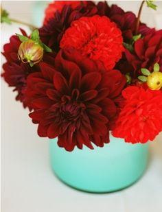 red flowers in aqua vase