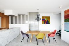 A trio of colorful chairs and the Foscarini Allegretto Suspension Lamp make for…