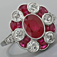 so elegantly done with the redshadow of petal done with two mixed-cut sotnes. subtle grace. the edge design on the platinum with tiny nicks is called millegrain, and adds to the delicacy without taking away from the strength of the ring, or the design... Art Deco Ruby and Diamond Ring