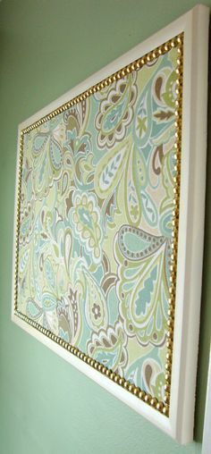 Large cork bulletin board/memo board covered in shades of green paisley fabric Trimmed with decorative gold nails and enclosed in a painted cream wooden frame. Perfect organizer for your home or office! The message center lets you display photos, cards, shopping lists, memos, notes, etc., in a stylish way. Measures 17 in. x 23 in. Includes mounting hardware.