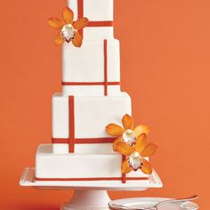 A plaid-inspired orange pattern takes on a modern look when set against tall, square wedding cake tiers. Sugar-made white orchids finish it off.