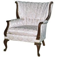 White Wing Chair ...............    The upholstered wing chair has a mahogany frame in the Chippendale style. It still has its original silk damask upholstery. It was produced as one of a matching pair, though your family may not have purchased its mate. The lines are derived from the 18th-century Chippendale period. It also features the undulating curves of the early-20th-century Art Nouveau style, seen in the chair's wings. The seat reflects the Art Deco style.