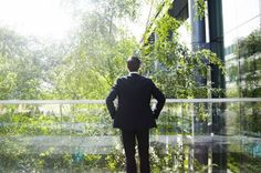 Business man looking out on trees from office balcony
