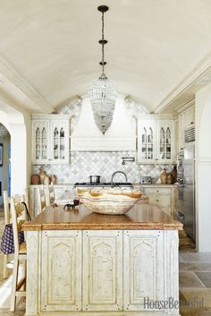A teardrop chandelier adds a glamorous note to the kitchen. Handmade Arabesque tiles form the backsplash.