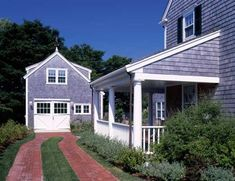 A classic double-track driveway runs to the detached garage; brick and weathered cedar shingles are ubiquitous on Nantucket.
