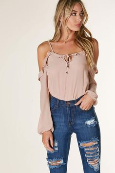 Lightweight long sleeve blouse with cold shoulder design and adjustable spaghetti straps. Flirty ruffle trim at neckline with front tie detailing.