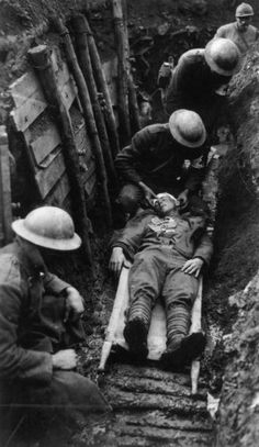 22nd March 1918: Red Cross workers in a trench tending to a wounded American soldier on a stretcher. (Photo by Sgt Leon H. Caverly/Topical Press Agency/Getty Images)