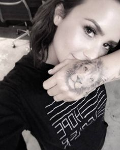 Demi Lovato's black and grey style lion portrait tattoo on her left hand. Tattoo Artist: Bang Bang · Keith McCurdy