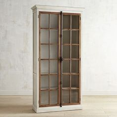 """Originating in 19th century Europe, the """"Cremone bolt"""" is a traditional casement-window locking device with a latch/handle mechanism. Featured on all our hand-hewn Cremone cabinetry, it's as beautiful as it is functional. Also featured: Antique white wood frames with protracted crown molding, contrasting natural wood casements and tempered pane-glass windows. Over 8' tall, our cabinet houses five adjustable shelves."""