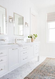 A long custom dual bath vanity in a white finish accented with nickel pulls topped with white quartz countertops and backsplash mounted polished nickel faucets.
