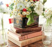 "Stack of books for centerpieces; for ""Welcome Party"" and ""After party""; will be placed by the mason jars on top of burlap and lace"