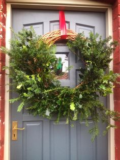 A Christmas wreath set against door in Farrow & Ball Down Pipe and Hardwick White on the frame