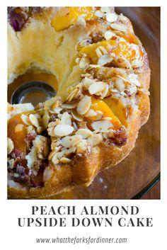 Pretty bundt cake with ripe juicy peaches and almonds in a pristine white cake.