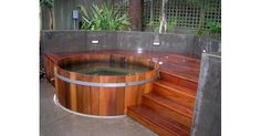Northern Lights cedar hot tub integrated in a pation with easy access from the raised deck.