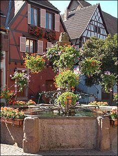 La fontaine place du marché à Bergheim - Place du Marché : la promenade vous conduit ici, à l'ancienne place d'Arme, bordée par la mairie et de belles maisons. Sur la place, une fontaine, en grès et ferronnerie, porte à son sommet l'un des symboles de la ville, que l'on retrouve sur son blason, la représentation du Berg (colline) de Bergheim. Poursuivez votre chemin vers la porte Haute en empruntant la Grand Rue.