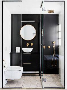 As dimensões compactas do banheiro não impediram a arquiteta Maayan Zusman de criar um espaço confortável e repleto de estilo! A parede preta brincou com o volume do espaço, destacando todo o brilho e contraste dos metais em latão.