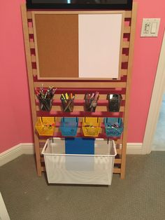 Crib railing supply station for school, digital and art supplies. I repurposed the drop side from my children's crib and leaned it against the wall. All bins are wire ones with small holes. I used pliers to make slightly bigger holes and hung bins with zip ties. Dry erase and cork board was hung with 3M Velcro picture hangers.