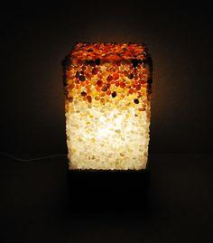 Luminária retangular (20x20x39 cm) Superfície musiva realizada em técnica direta, utilizando pedras roladas semipreciosas (ágata vermelha, ágata natural, cornalina, citrino, cristal e ônix) com acabamento misto (brilhante e opaco). Estrutura em madeira, acrílico e iluminação LED.
