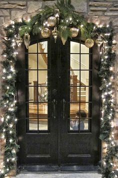 Christmas greenery around front door, with large ornaments at the top