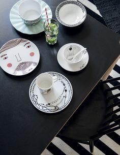 Suvi rakastaa leikkisiä astioita. Jo tuotannosta poistettu Marimekon Aarre-lautanen on yksi suosikeista. Donna Wilsonin mieskasvoinen lautanen on hauska. Mintunvärisen Napoli-lautasen reunat menevät vekeille. Arabian Piilopaikka-lautaset ovat joululahja äidiltä. Ylhäällä vasemmalla Marimekon Kulkue-muki. Esther Horchnerin suunnittelemissa Pols Pottenin kupeissa uiskentelee naishahmoja.
