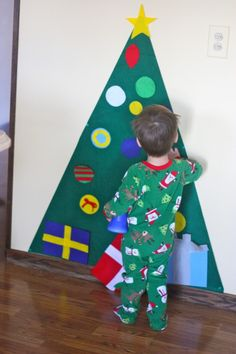 Kid-Friendly Christmas Tree  You need 1 yard of green felt. Decide how high you wanted tree be & cut a straight line across the felt. Then fold the felt piece in half & use a straight-edge to trace the angled cut. Next use push-pins to attach it to the wall. Then cut out circles, for ornaments using a cup for a template. Leave some ornaments plain & use a hot glue gun to add stripes or polka dots to others. Children will love getting to decorate & redecorate their very own Christmas tree!
