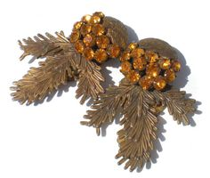 Dress clips were incredibly popular during the depression era due to their versatility! Here we have a pair of wonderful dress clips in a pine design accentuated with golden rhinestones, all prong-secured and sparkling. You will receive both dress clips.  Measurements: 2 Long x about 1 1/2 Wide (at widest point)  Please be sure to check out my shop for a *~HUGE~* variety of vintage and antique jewelry that has FREE additional shipping.