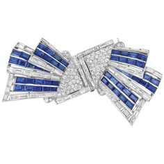 Art Deco Platinum, Sapphire and Diamond Double Clip-Brooch   Topped by triangle-shaped plaques, supporting staggered ribbons, set throughout with 80 round and 68 baguette diamonds approximately 11.20 cts., accented by bands of 50 rectangular-cut sapphires approximately 13.00 cts., can be arranged at varied angles, circa 1930, approximately 22 dwt.