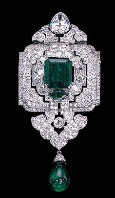 CIRCA 1927 ART DECO EMERALD AND DIAMOND PENDANT/BROOCH, BY CARTIER  Designed as an old European and old mine-cut diamond openwork panel with a central rectangular-cut emerald weighing 12.28 carats, suspending a diamond palmette and emerald bead drop, to the pear-shaped diamond surmount.