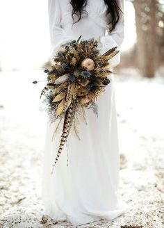 A rustic bouquet of thistles and feathers is a beautiful addition to your cold weather celebration. Winter Wedding Bouquet Ideas