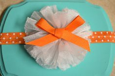 Orange polka dot band with white ballerina flower and orange bow  on Etsy, $7.00