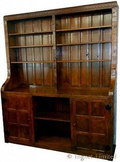 An important early and rare Robert Mouseman Thompson Adzed Oak Bookcase The top with an arcade castellated carved frieze decoration with massive one piece solid uprights supporting six shelves Base with panelled burr oak cupboards flanking an open shelf to centre panelled back all major surfaces with adzed finishes carved with two mouse signatures original … Robert Thompson, Oak Cupboard, Arts And Crafts Movement, William Morris, Cupboards, Open Shelving, Arcade, Tall Cabinet Storage, Centre