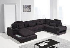 The modern fabric sectional sofa is designed with a veneer ledge for drinks and log-shaped headrests. It features a contemporary built-in light giving off an ambient glow beside the chaise that slopes