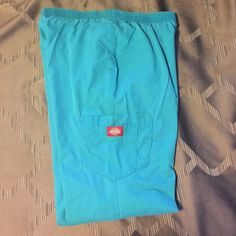Dickies scrub pants, medium Has elastic band around the whole waist. It has the side pockets with one of them having a dual pocket. Has a three inch slit on bottom of pants. Has a nickel size bleach spot on the right pant leg on the bottom and several tiny white spots, see last picture. Selling cheap due to that reason. Very comfortable pants. Waist measures 14.5 inches, inseam is 31 inches. Turquoise color. Any questions please let me know. Dickies Pants