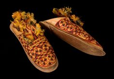 2 Shoes (a,b). Made of leather, with heavy silk embroidery in red, green, and black all over the upper surface. Tongue of shoe is long, decorated with embroidery, and with green, black, red and yellow tassels. Back of shoes is nailed to bottom with strip of red leather. Worn by aristocrats. (Suno harilbe). L. 11 1/4'. Kanuri, Western Sudan Red Green, Yellow, Body Adornment, Ants, Red Leather, Tassels, Surface, Footwear, Embroidery