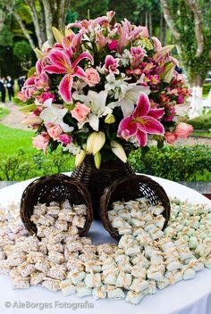 Mesa de bem-casados com cestas de vime e arranjo de flores.