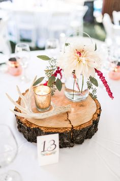Boho chic + forest wedding centerpiece idea - wooden tree slices, candle votives, antlers + glass mason jars filled with dahlias and wildflowers {Jacquelynn Brynn Photography}