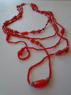 Collar de tres cordones con diferentes largos, realizado con piedras de diferentes rojos, rayados y piedras.