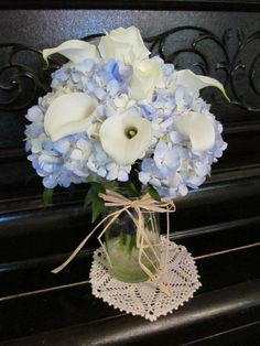 Wedding bouquet of blue hydrangea, white calla lilies, and white roses