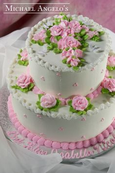 Traditional Roses #42Religious This is a traditional design within this category with the two tiers iced in buttercream and accented with pink roses. The top of the cake is beautifullly decorated with roses in the shape of a cross. Perfect for any religious celebrations.